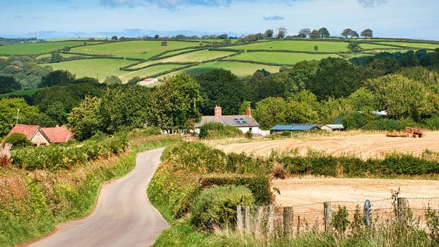 A country cottage and farm surrounded by open fields in the English countryside.